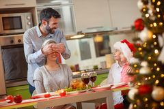 Christmas dinner- happy father and children surprises mother. Christmas dinner- happy smiling father and children surprises mother Stock Photography