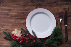 Christmas dinner plate. Christmas dinner background, plate on dark rustic wooden table wth Christmas decoration, top view stock image