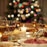 Christmas dinner is ready. Beautiful dining table full of a variety of delicious festive food and wine with a Christmas tree in the background in warm mood Stock Photo