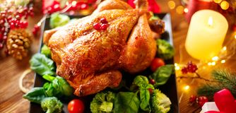 Christmas dinner. Roasted chicken on holiday served table, decorated with gifts and burning candles. Roasted turkey royalty free stock photo
