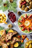 Christmas dinner with roasted meat steak, Christmas Wreath salad, baked potato, grilled vegetables, cranberry sauce. Delicious Christmas meal with roasted meat royalty free stock image