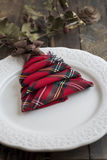 Christmas Dinner rustic, white plate and napkin green and red bo. Xes in the shape of tree Stock Photo
