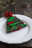 Christmas Dinner rustic, white plate and napkin green and red bo Stock Image