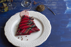 Christmas Dinner rustic, white plate, and napkin red boxes in th. E shape of tree, Blue background Stock Photo