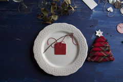 Christmas Dinner rustic, white plate, and napkin red boxes in th. E shape of tree, Blue background Royalty Free Stock Image