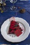 Christmas Dinner rustic, white plate, and napkin red boxes in th. E shape of tree, Blue background Stock Images