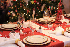Christmas dinner table. A set table for christmas night dinner, tree in background Royalty Free Stock Photo