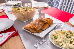 Christmas dinner table with fried salmon fillets and eggs mayonnaise. Dining salad dish banquet bright china vegs herrings vegetables cloth fish marinated stock photography
