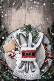Christmas dinner table place setting with plate, cutlery, fir branches , snow, blank tag mock up and snowman on rustic wooden. Background. Layout for holiday stock photography