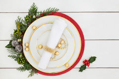 Christmas Dinner Table Setting. With porcelain plates, napkin, decorations and foil wrapped chocolates, with holly, mistletoe, ivy and cedar leaves on Royalty Free Stock Image