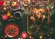 Christmas dinner table with whole roasted turkey, stuffed with dried fruits served in roasting pan with sauce,red plates, cutlery. Decoration and burning royalty free stock photo