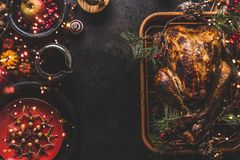 Christmas dinner table with whole roasted turkey, stuffed with dried fruits served with sauce,red plates, cutlery, decoration and. Burning candles, top view stock photos