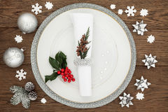 Christmas Dinner Time. With plate, napkin, sparkling silver bauble decorations, holly and winter greenery over oak table background Stock Photography