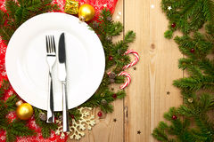 Christmas Dinner - white plate with cutlery on wooden background Royalty Free Stock Photo