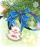 Christmas discount coupon and fir tree branches. Ribbon, bow with a discount coupon and fir tree branches on a sparkling  holiday background. Festive Christmas Stock Photo