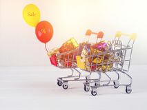 Christmas discount, Little shopping cart full of christmas gifts, Shopping trolley with gift boxes stock photos