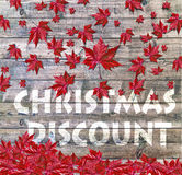 Christmas Discount and red falling leaves laying on wooden background Stock Photography