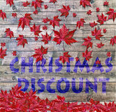 Christmas Discount and red falling leaves laying on wooden background Royalty Free Stock Photos