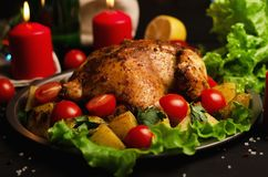 Christmas dish. Xmas baked whole chicken with tomatoes and potatoes close-up stock photo