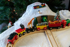 Christmas train set with African animals. Christmas display featuring generic wooden train set, plastic, African animals, fake snow and a Christmas tree and royalty free stock photos