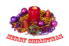 Christmas display with a red candle burning in the middle of chains and baubles Royalty Free Stock Photo