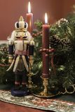 Christmas display with nutcracker and lit candles. Christmas display showing nutcracker and lit red candles in brass holders in front of greenery and pine cones Royalty Free Stock Photography