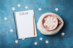 Christmas do list and cup of hot cocoa decorated knitted scarf with marshmallow on vintage turquoise table top view. Flat lay. Royalty Free Stock Photos