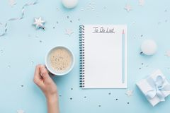 Christmas do list and woman hand with cup of coffee on blue pastel table top view. Flat lay style. Holiday planning. Christmas do list and woman hand with cup royalty free stock images
