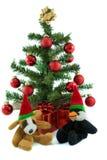 Christmas Dog and Penguin. Cuddly christmas Dog and Penguin with christmas tree and presents Stock Photo