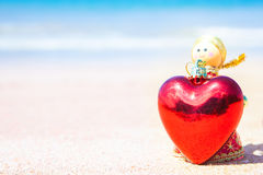 Christmas doll an angel give a Heart on the sand beach and blue Royalty Free Stock Images