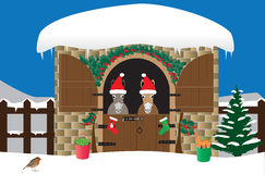 Christmas Donkeys. Two Donkeys in Santa Hats in a snow covered stable decorated with holly and a xmas tree Royalty Free Stock Image