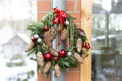 Christmas door wreath with pines and Christmas decorations. In a natural light royalty free stock images