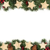 Christmas double border of branches with rustic wood star ornaments over white Royalty Free Stock Image