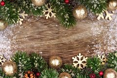 Christmas double border with gold ornaments, branches on rustic wood Royalty Free Stock Images