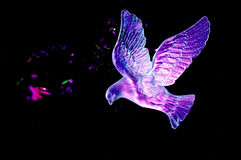 Christmas dove. Backlit Christmas dove decoration with colorful bokeh and black background Royalty Free Stock Image