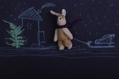 Christmas drawing with chalk on a black background with a rabbit. Toy and christmas tree Royalty Free Stock Photography