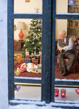 Christmas dream. Grandfather looking at his asleep grandchild under the Christmas tree Royalty Free Stock Image
