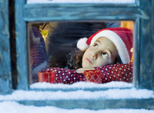 Christmas dream. Little girl with a Santa hat  looking outside Royalty Free Stock Photography
