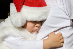 Christmas dream. The small child in a Santa�s hat sleeps on mum's hands Stock Images
