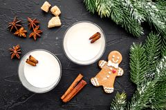 Christmas drink cooking eggnog in glasses for celebration with cinnamon and spruce black table background flat lay. Christmas drink cooking eggnog in glasses for Stock Photos