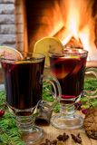 Mulled wine glintwine in drinking glasses and christmas decorations, against cozy fireplace background. Christmas drink. Cozy fireplace concept. Mulled wine stock image