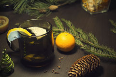 Christmas drink on a decorate wooden table. Christmas drink with lemon on a decorate wood table with mandarin, pine branches and cone Stock Photos
