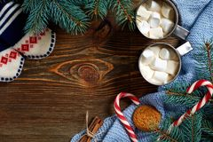 Christmas drink. Mug hot coffee with marshmallow, red candy cane on the wooden background. New Year. Stock Images