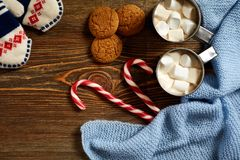 Christmas drink. Mug hot coffee with marshmallow, red candy cane on the wooden background. New Year. Royalty Free Stock Photo