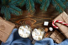 Christmas drink. Mug hot coffee with marshmallow, red candy cane on the wooden background. New Year. Royalty Free Stock Image