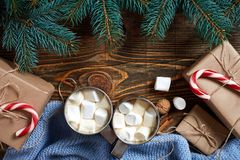Christmas drink. Mug hot coffee with marshmallow, red candy cane on the wooden background. New Year. Stock Photography