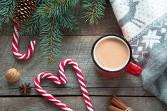 Christmas drink. Mug hot coffee with milk, red candy cane on the wooden background. New Year. Holiday card. Rustic style. Top view Royalty Free Stock Photography