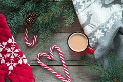 Christmas drink. Mug hot coffee with milk, red candy cane on the wooden background. New Year. Holiday card. Rustic style. Top view. And copy space Stock Photos