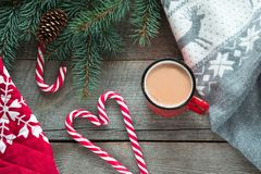 Christmas drink. Mug hot coffee with milk, red candy cane on the wooden background. New Year. Holiday card. Rustic style. Top view Royalty Free Stock Photos