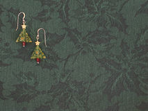Christmas earrings. On holly-pattern fabric Royalty Free Stock Photo